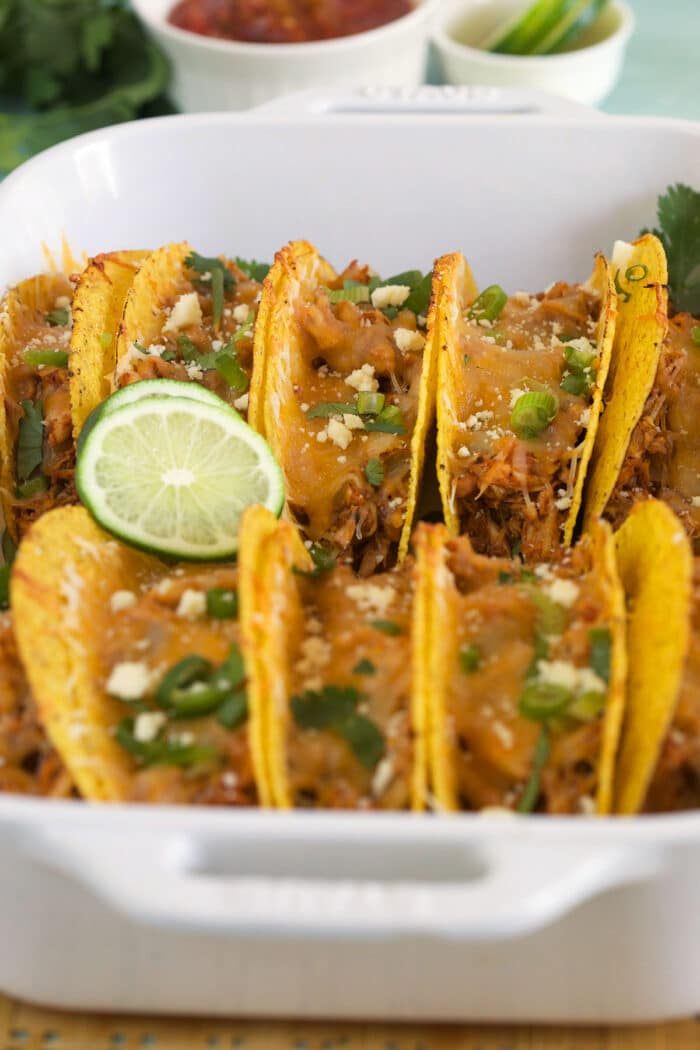 Sliced limes are placed on top of baked tacos in a white dish.