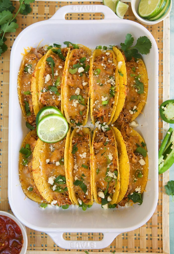 Ten tacos are placed in a large baking dish.
