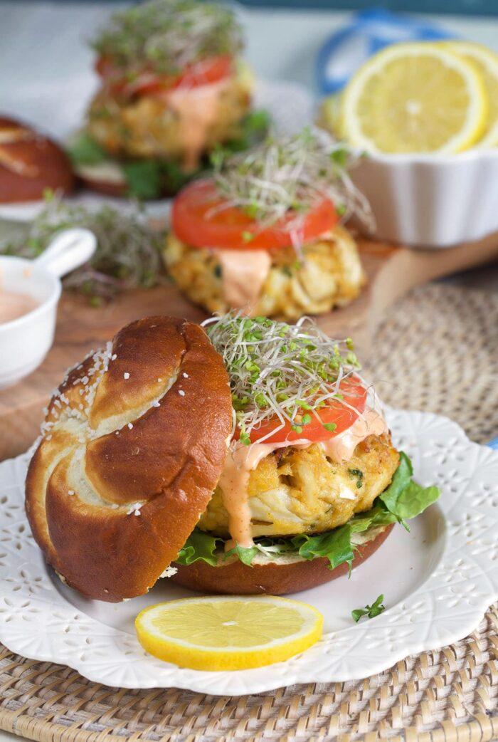 A pretzel bun is placed beside a crab cake sandwich.