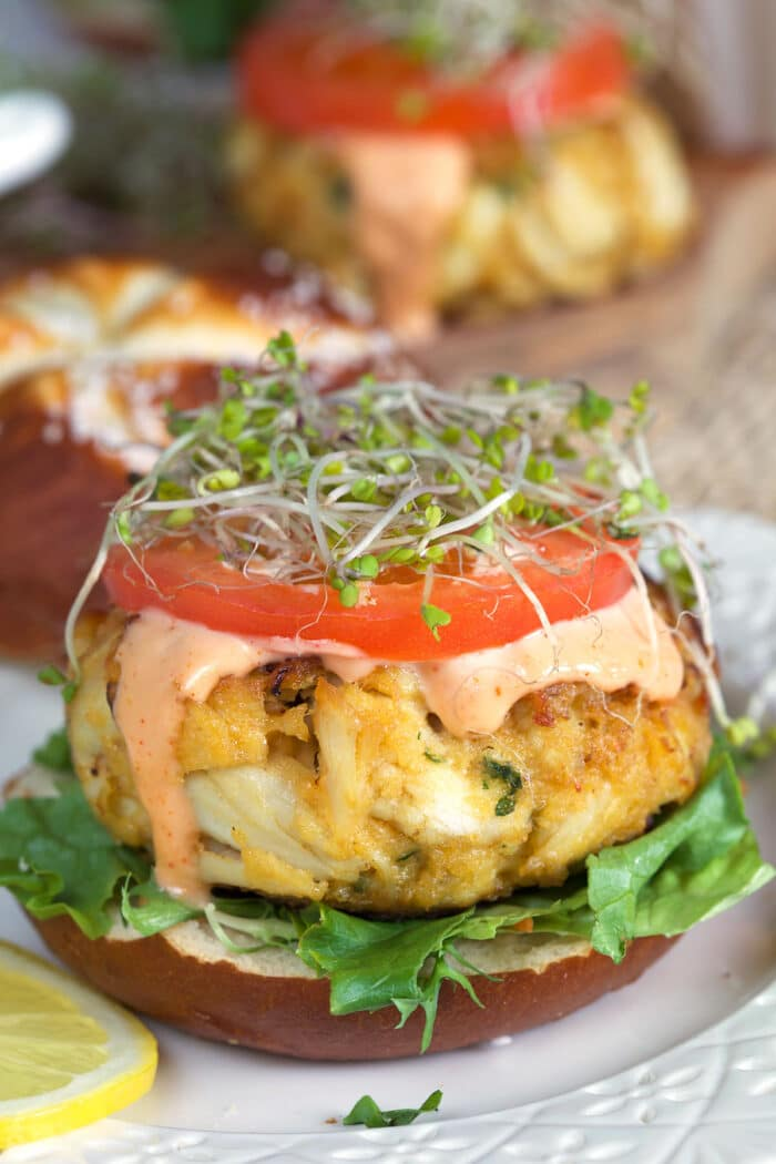 A crab cake is placed atop a bun and topped with tomato slice, sauce and micro greens.