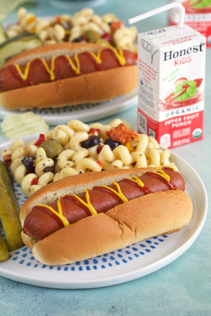 A hot dog is placed next to pickle spears and macaroni salad.