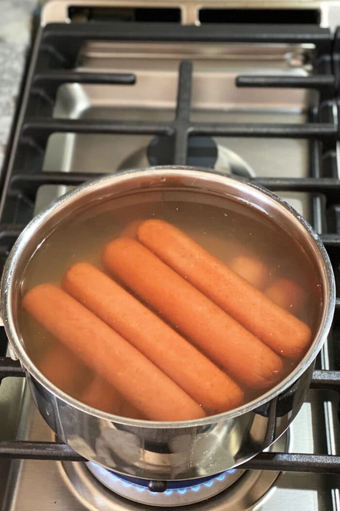 Hot dogs are being boiled on a stovetop.