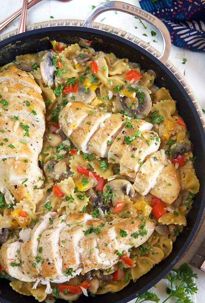 Three sliced chicken breasts are in a skillet filled with cheesy pasta.