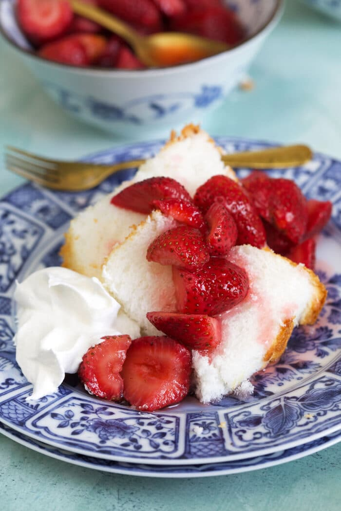 Pieces of cake are covered in macerated strawberries.