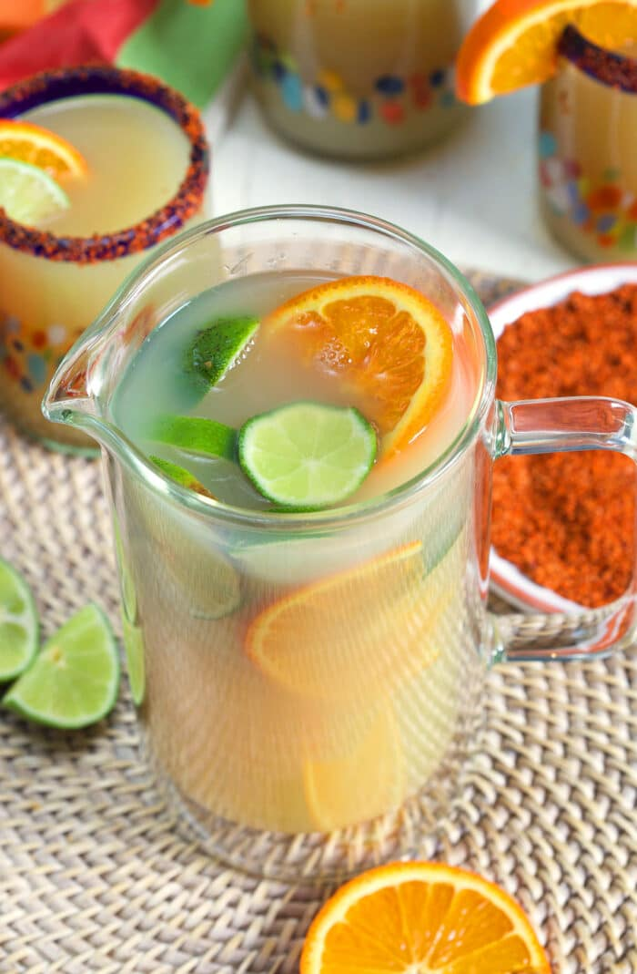 A glass pitched is filled with orange slices, lime slices, and margarita mix.