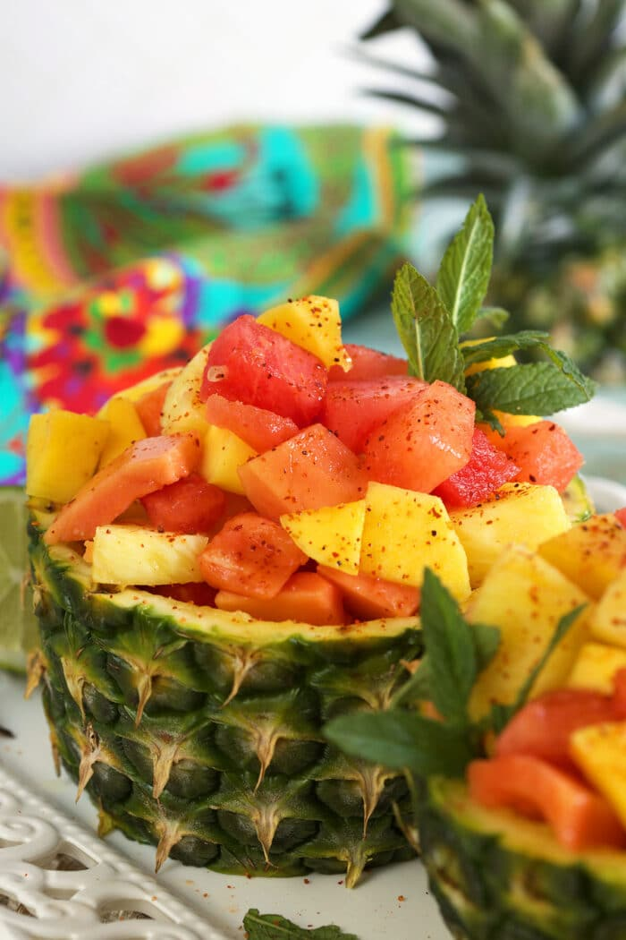A fruit salad is placed in half of a pineapple.