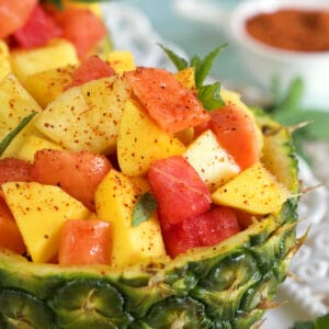 Powder is placed on top of fresh fruit in a pineapple bowl.