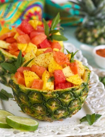 Two pineapple halves are filled with fresh fruit.