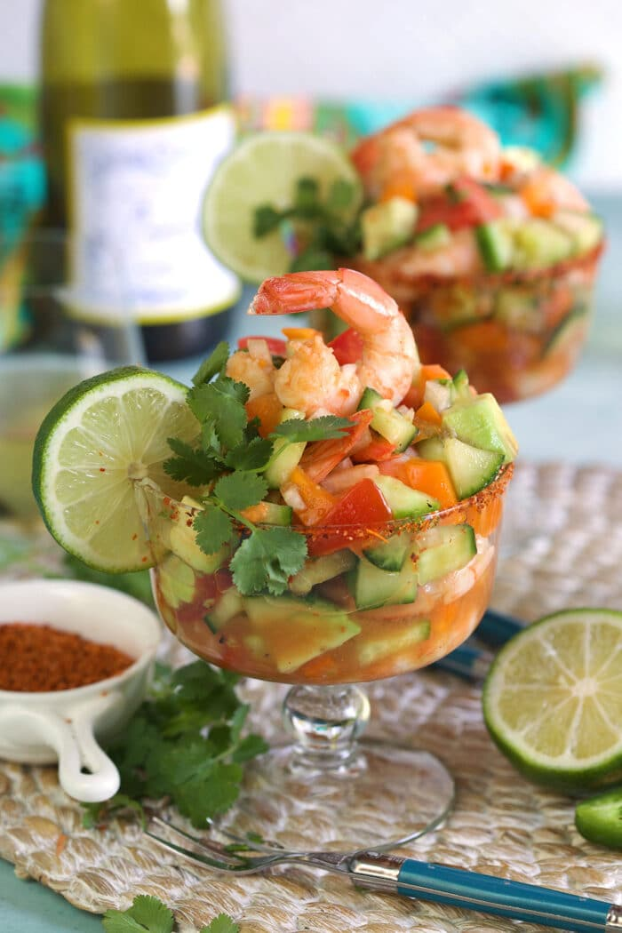 A shrimp cocktail is presented with a slice of lime on the side of the glass.