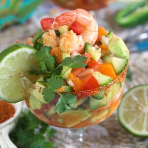 A lime and piece of cilantro garnish a shrimp cocktail.