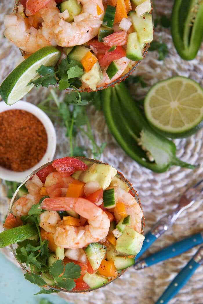 Fresh ingredients like limes and peppers are placed on a surface near Mexican shrimp cocktails.