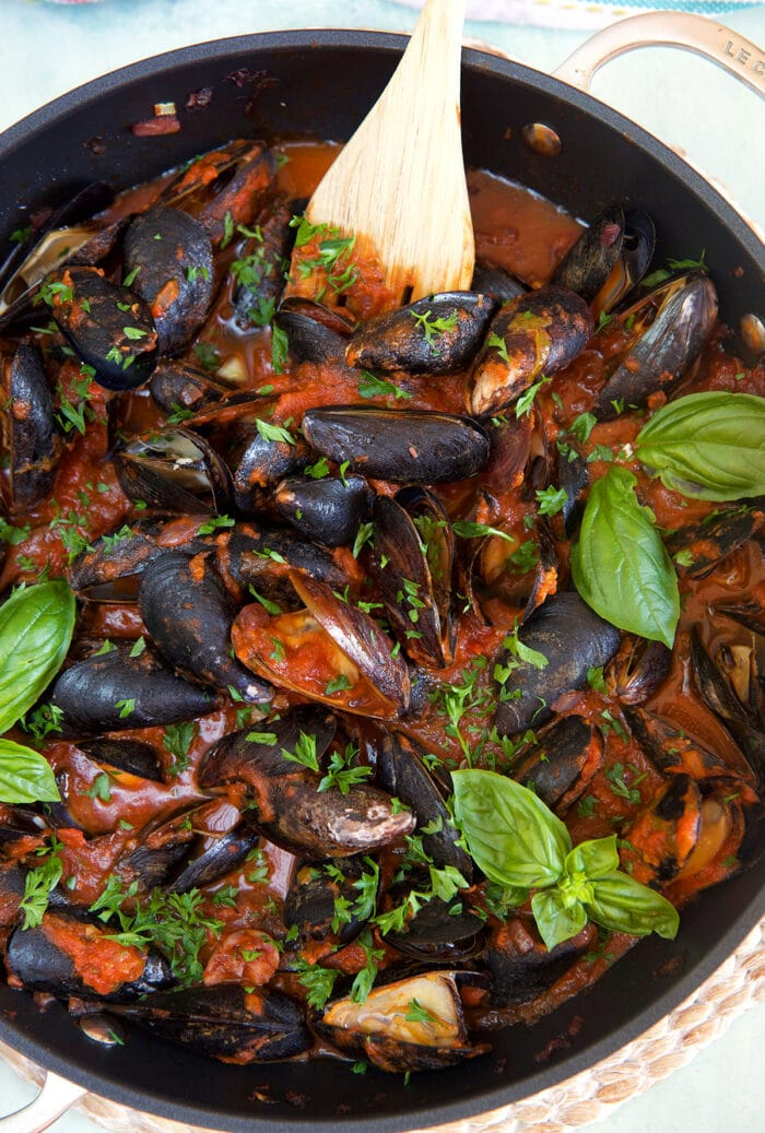 Mussels are being cooked in a large black skillet.