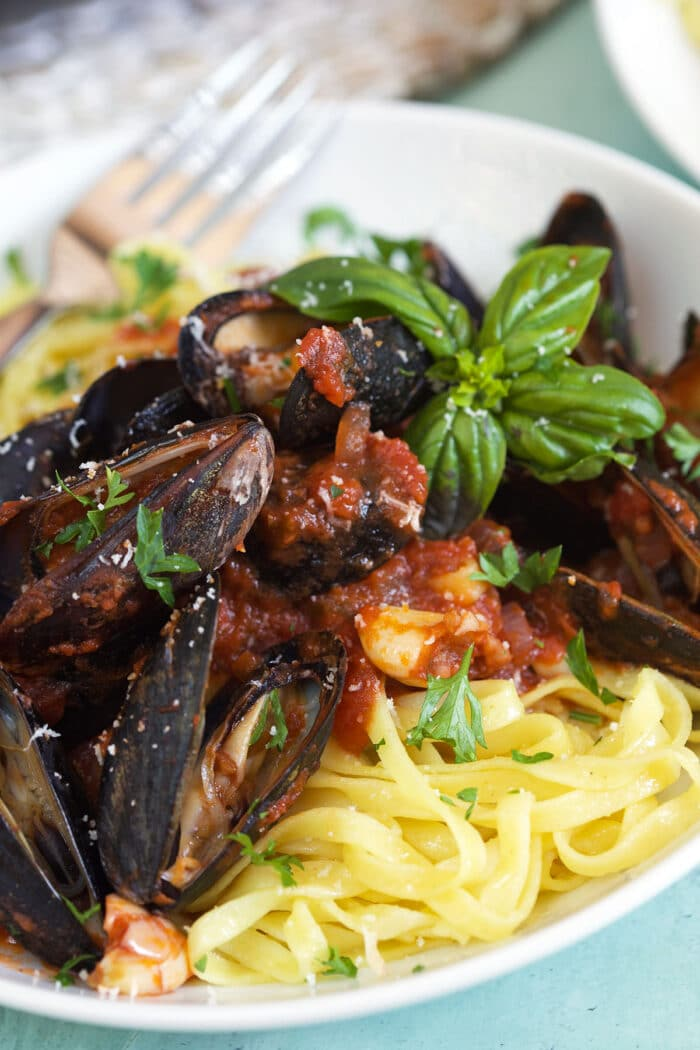 A plate of noodles is covered in marinara tossed mussels.