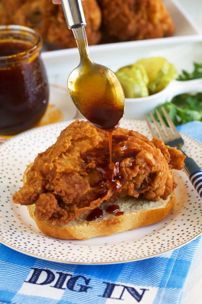 Nashville hot sauce is being drizzled over a piece of fried chicken.