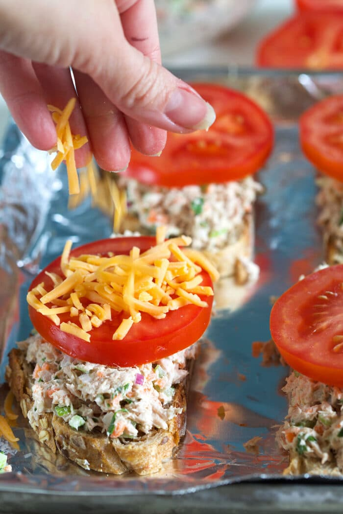 Cheese is being sprinkled onto an un-broiled tuna melt.