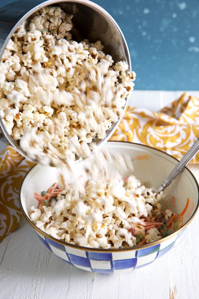 Popcorn is being added to a large bowl.