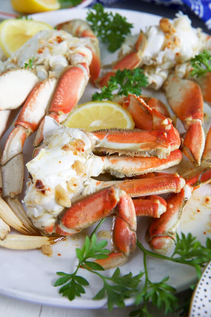 Crab legs are arranged on a plate next to a lemon slice.