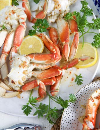 Several crab legs have been plated with herbs and lemon.
