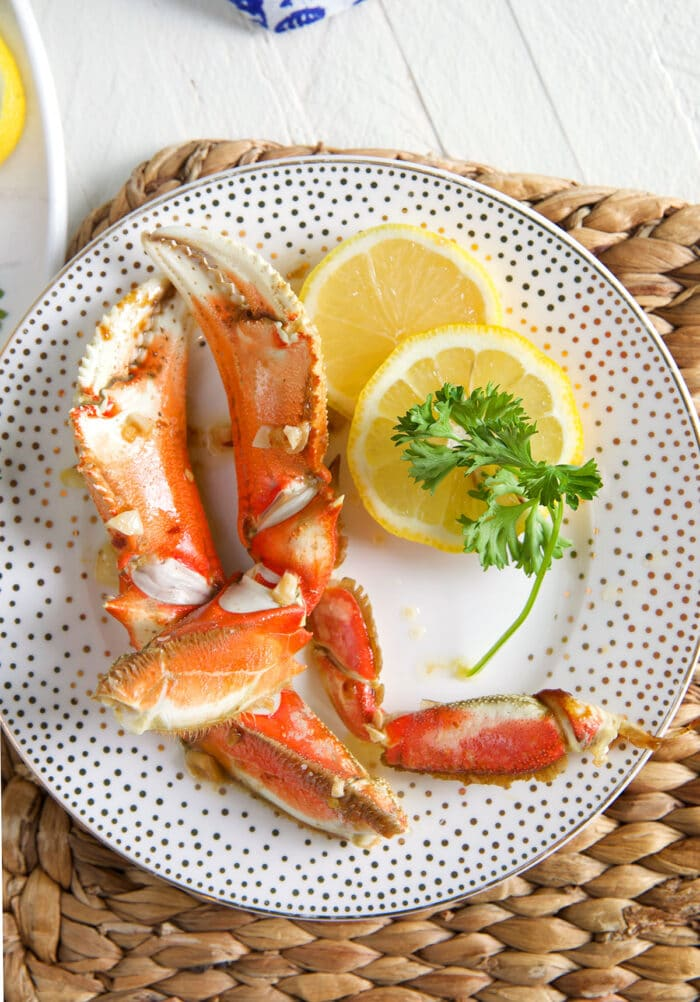 Two crab legs have been placed on a plate with lemon slices.