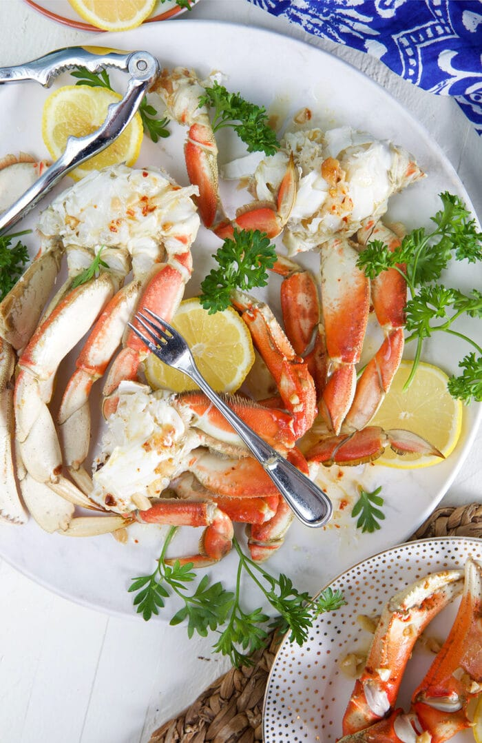 Several serving utensils are placed on a plate of crab legs.
