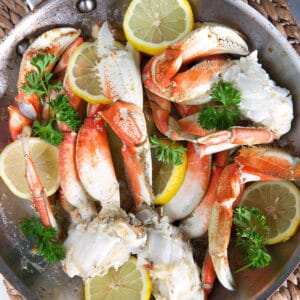 A pot of crab legs is filled also with lemon and herbs.