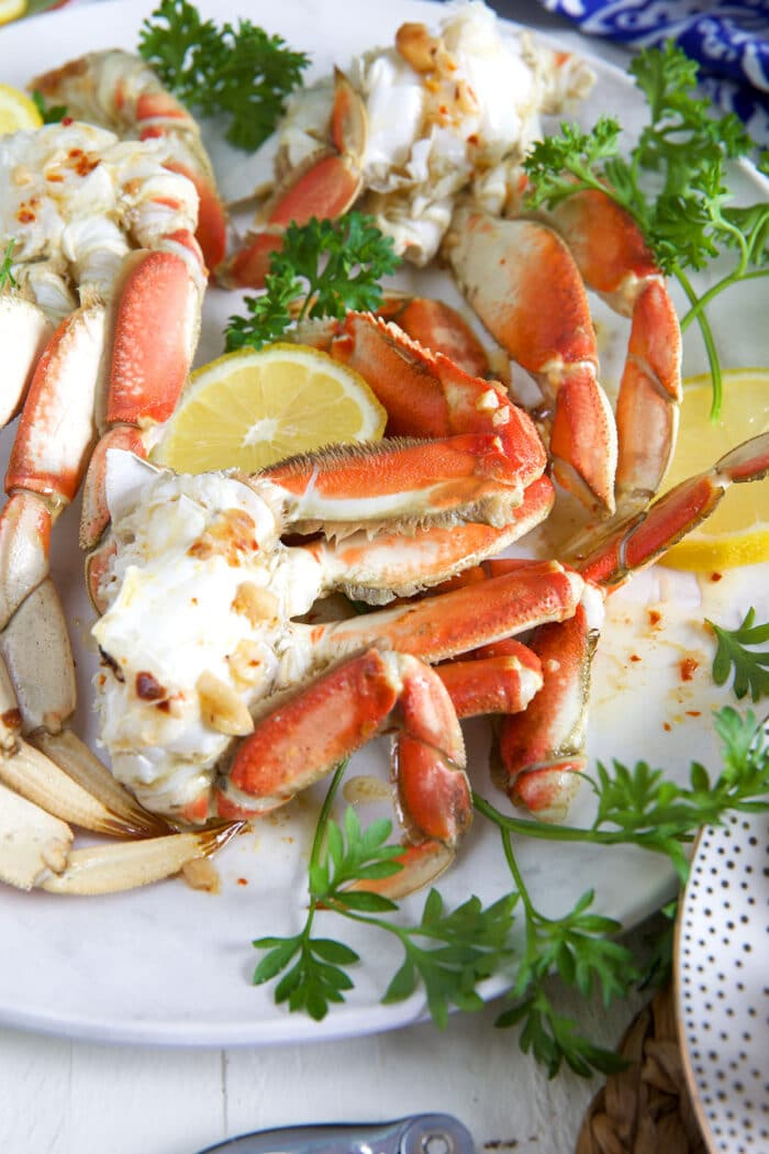 Crab legs are cooked and arranged on a white plate.