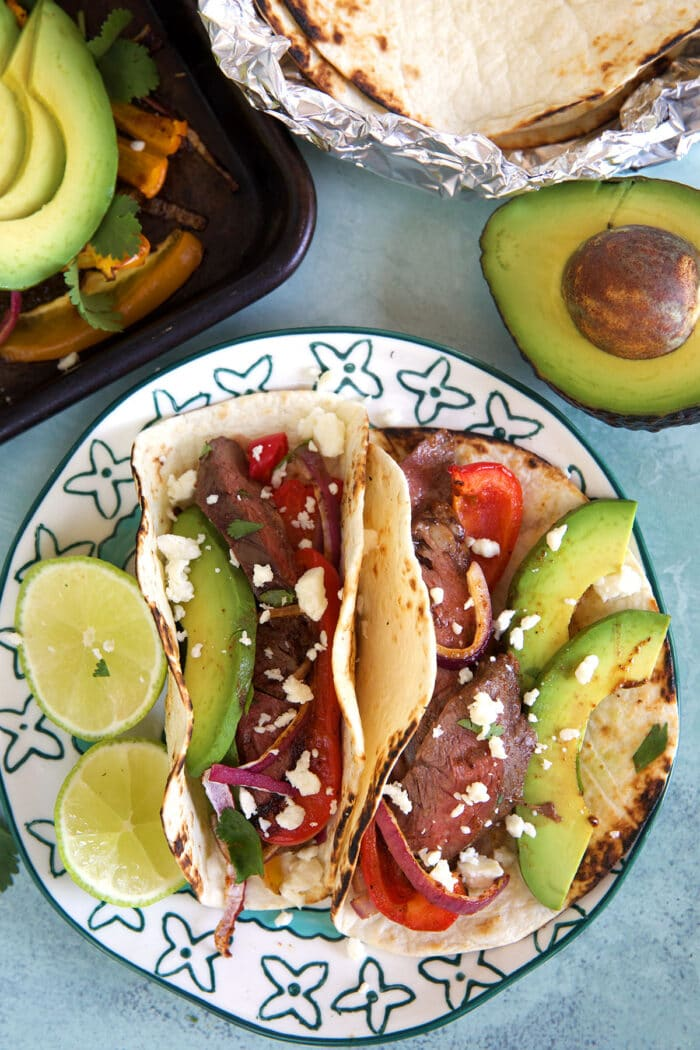 two steak fajitas on a plate on a white background with an avocado in the corner.