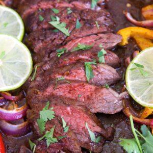 sliced steak on a sheet pan with fajita vegetables.