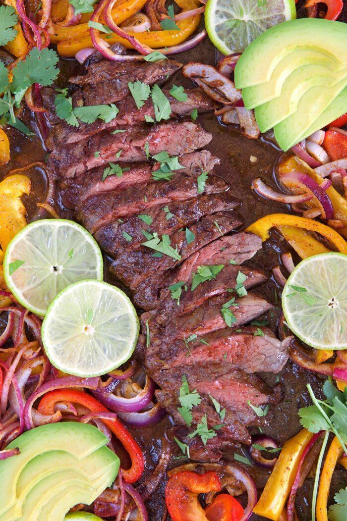 Sliced steak on a sheet pan with fajita vegetables, lime and avocado.