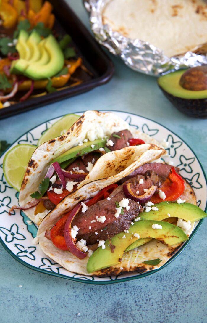 Two steak fajitas on a white plate with avocado