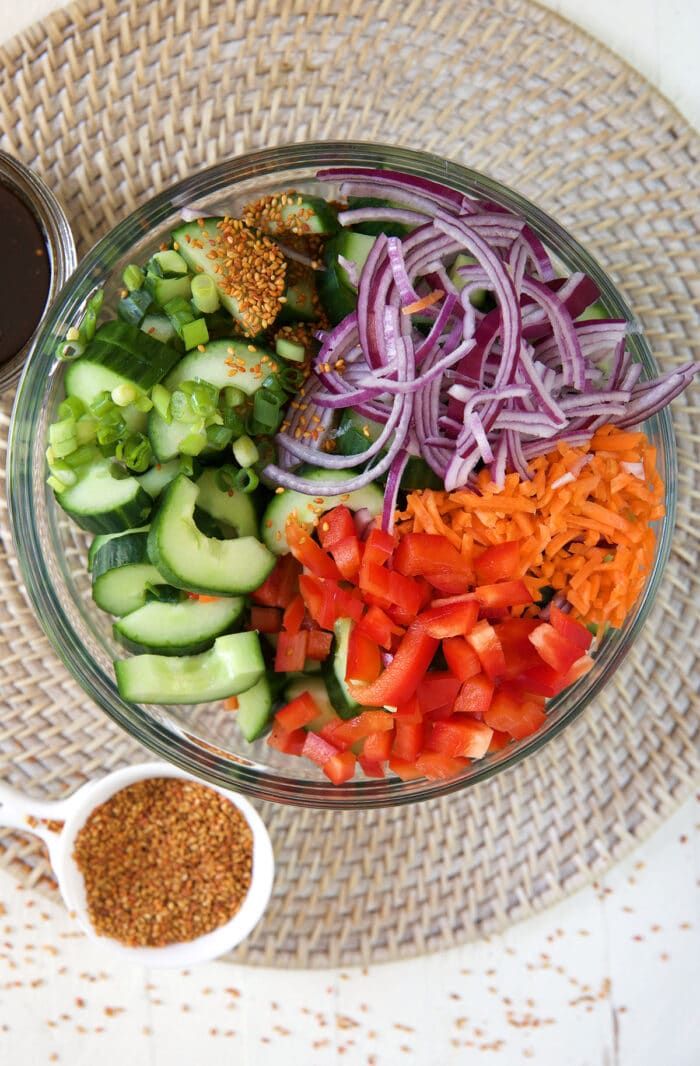 All of the ingredients for cucumber salad are in a large glass bowl.
