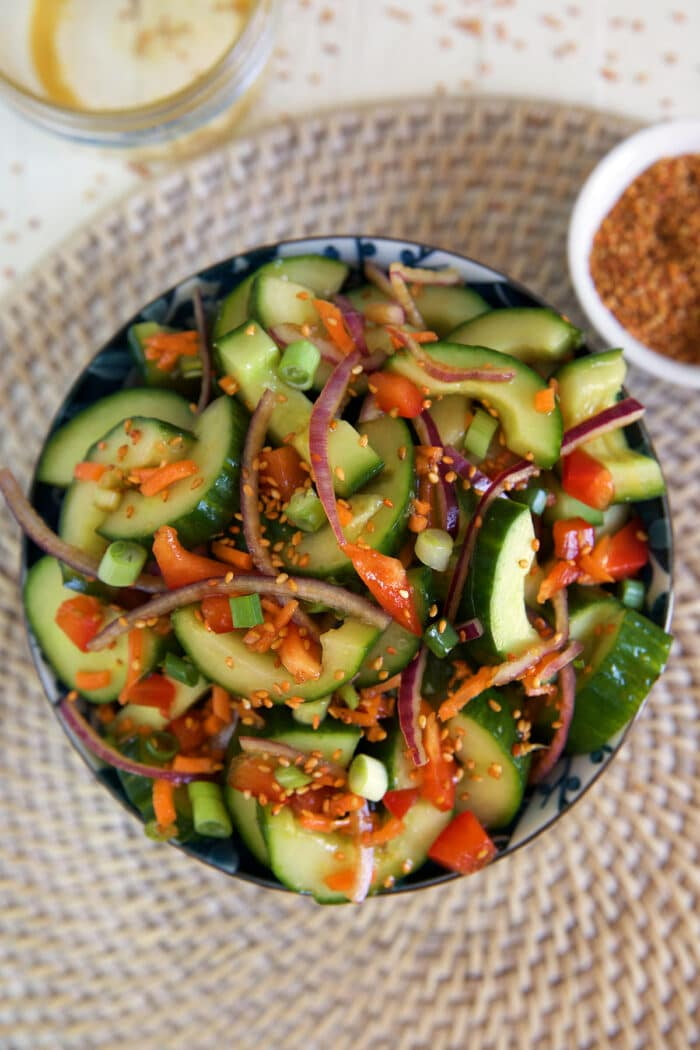 An asian cucumber salad has been tossed and is filling a blue and white serving bowl.