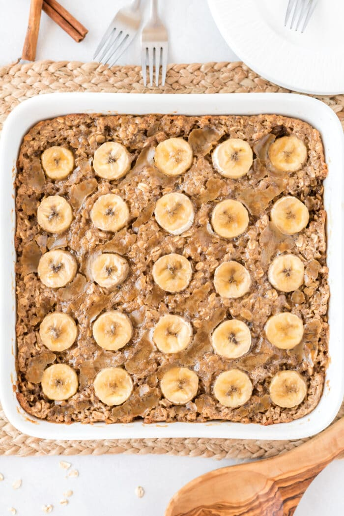 Bananas Foster Baked Oatmeal in a white baking dish with a white background and a wooden spoon on the side.