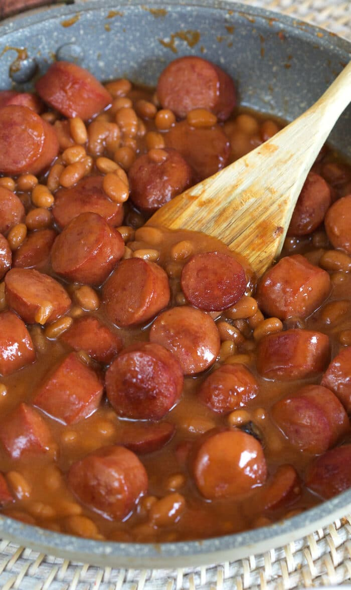 A wooden spoon is placed in the middle of a skillet filled with hot dogs and beans.