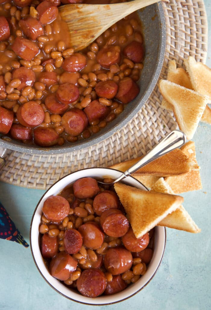 A piece of toast is in a small bowl filled with beans next to a large pot.