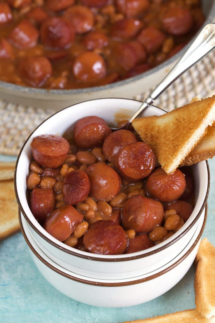 A serving of beanie weenies is in a small white bowl with a slice of bread on the side.