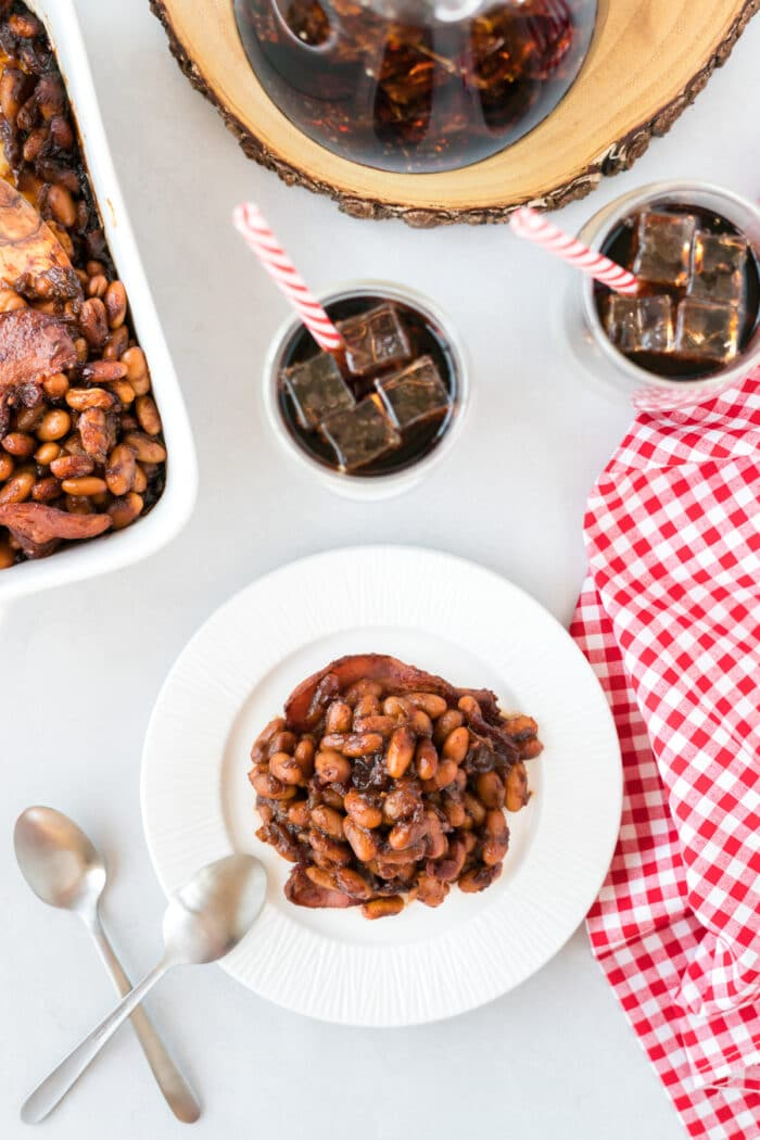 BBQ Baked Beans on a white plate with glasses of cola