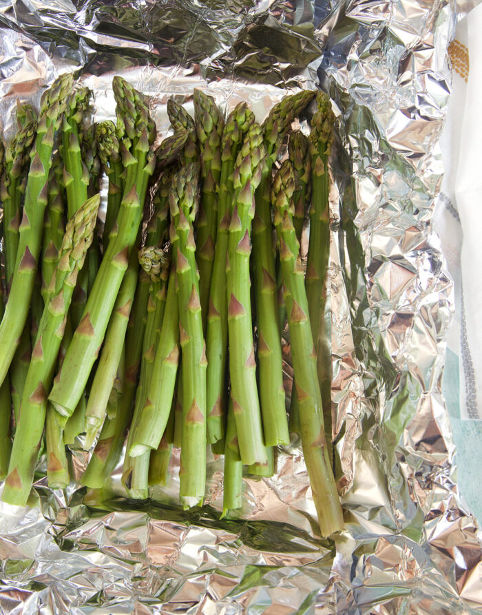 Uncooked asparagus is placed on foil.