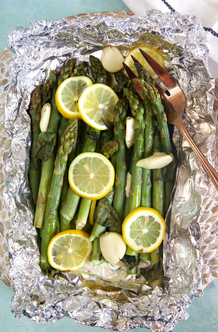 Asparagus is cooked and wrapped in foil, topped with lemon slices.