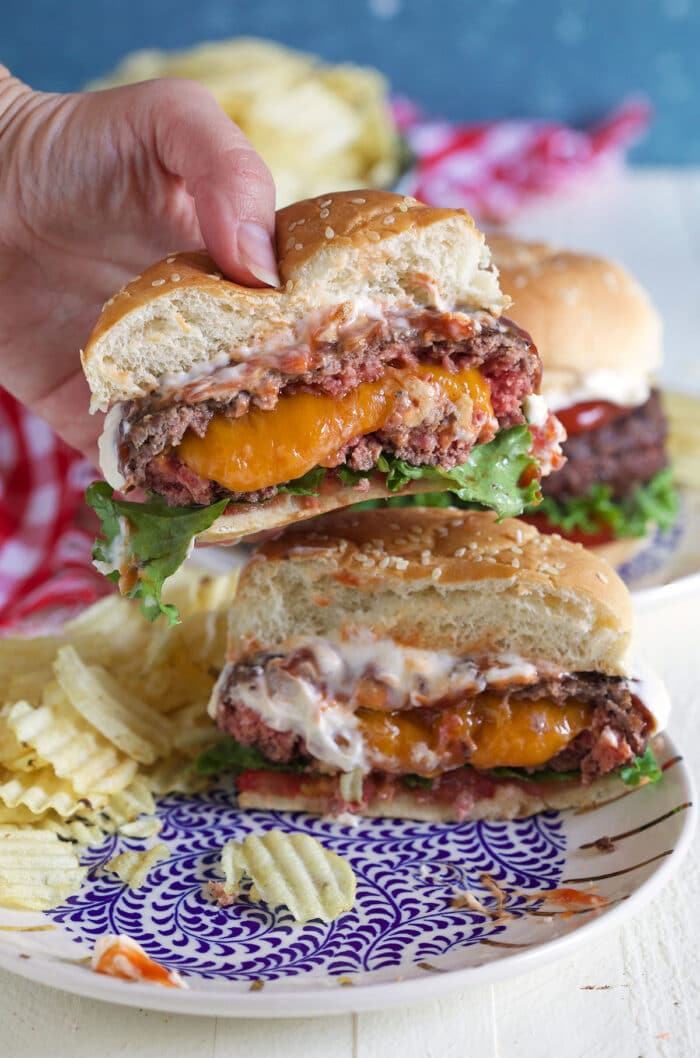 A burger has been cut in half to reveal a cheesy center.
