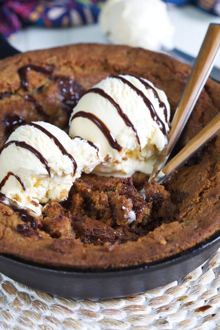 Two spoons are digging into a pizookie.