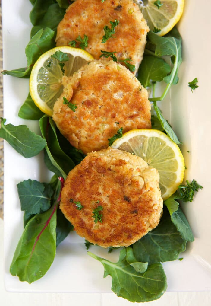Tuna patties are placed on a plate next to lemon slices and leafy greens.