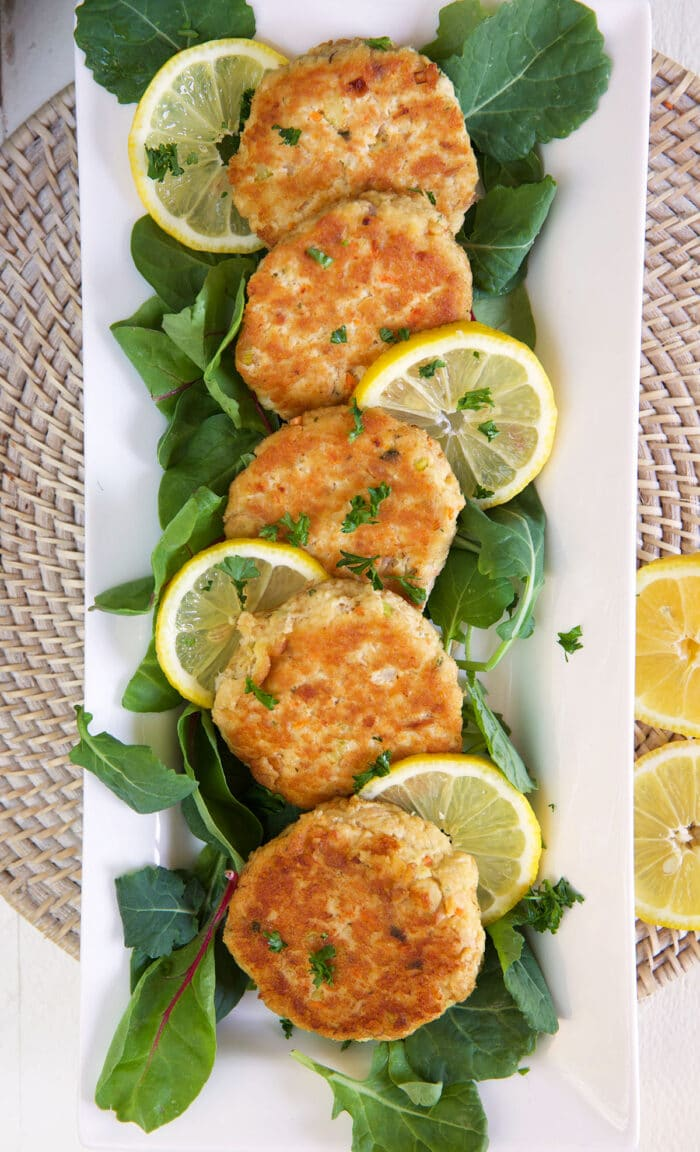 Five tuna patties are lined up on a long white serving plate.