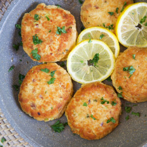 Tuna patties are arranged in a large skillet with lemon slices.