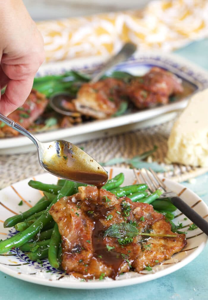Veal Saltimbocca with sauce being drizzled over top with a spoon.