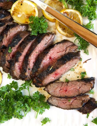 Slices of steak are on a white plate.