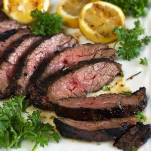 A sliced steak is placed next to herbs and lemon halves on a white plate.
