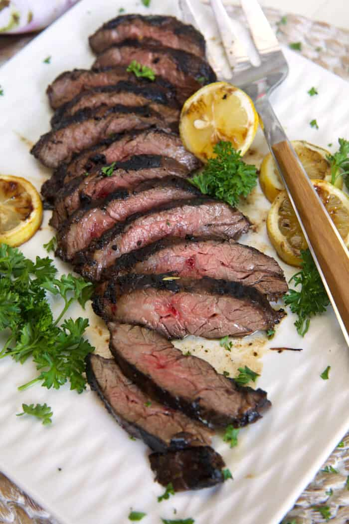 A large grilling fork is placed next to a sliced steak.