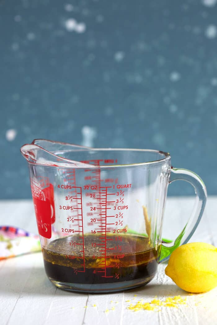 A measuring cup is placed next to a lemon on a white surface.