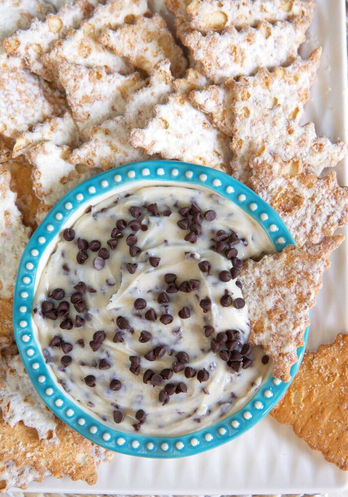 Many cannoli shells are placed around a small bowl.